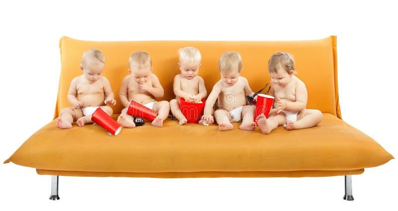 barn som äter den sittande sofaen för grupppopcorn arkivbild