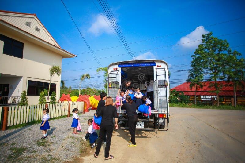 Barn som av får skolbussen av läraren royaltyfri bild
