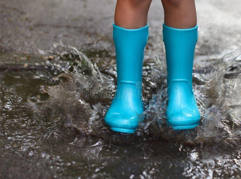 Barn som bär blåa regnkängor som hoppar in i en pöl royaltyfri foto