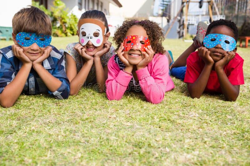 Barn som bär maskeringar som ligger på fält i gård royaltyfri foto