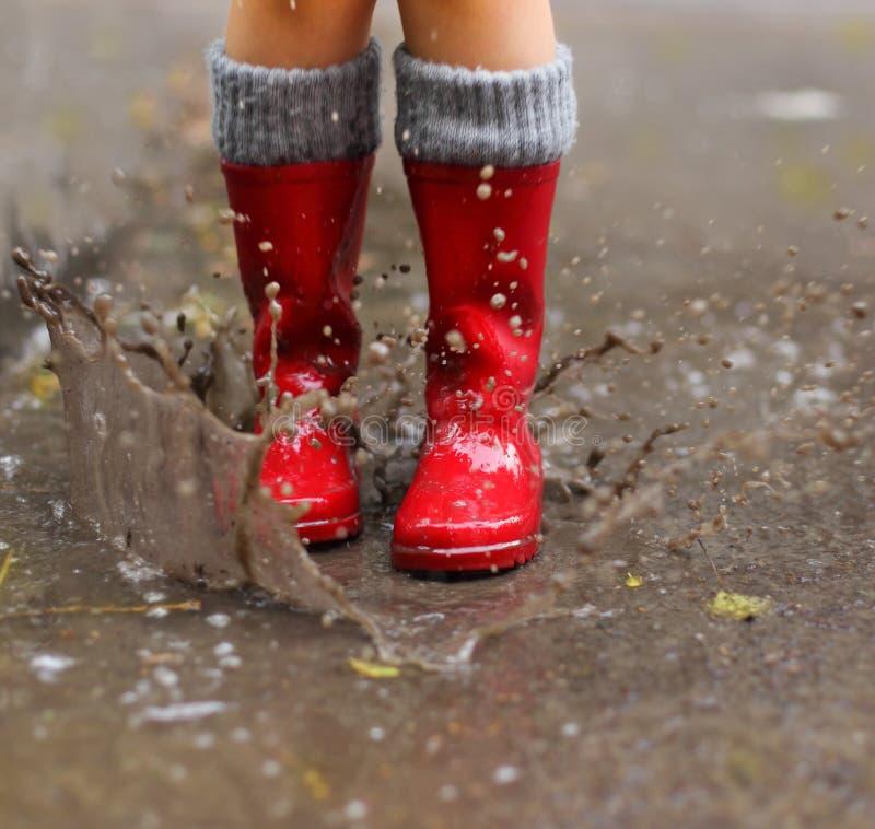 Barn som bär röda regnkängor som hoppar in i en pöl arkivbilder