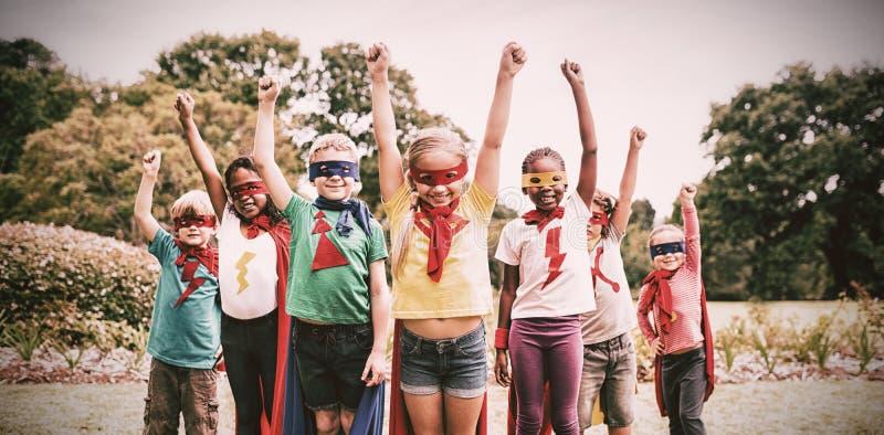 Barn som bär superherodräktanseende arkivbilder