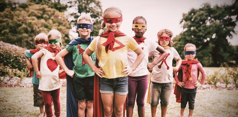 Barn som bär superherodräktanseende royaltyfria foton