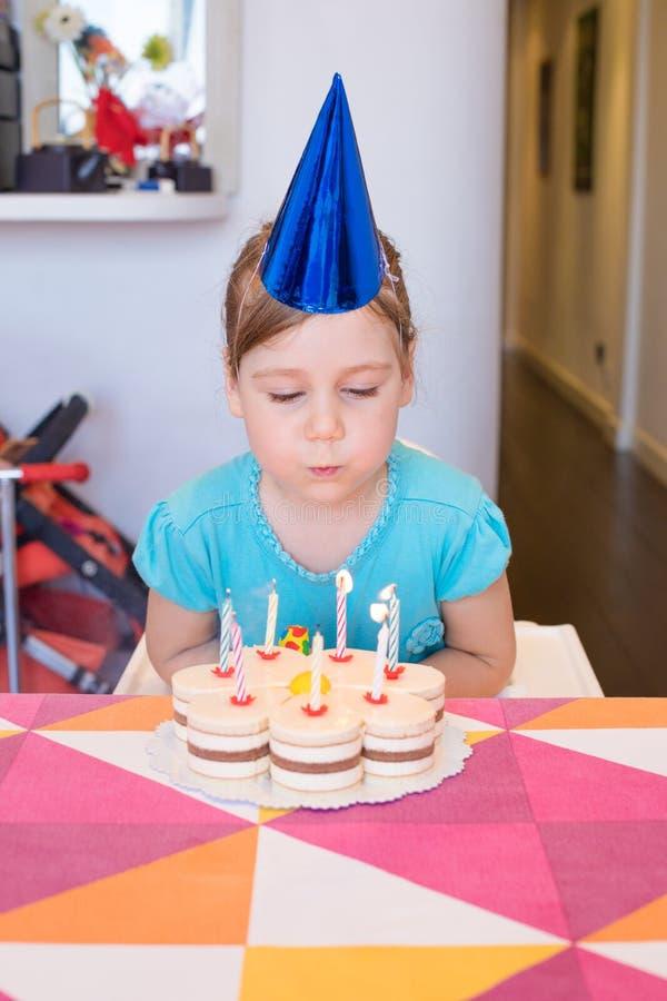 Barn som blåser brännande stearinljus på födelsedagkakan royaltyfri foto