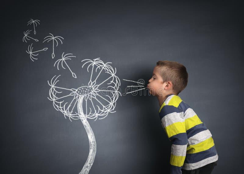 Barn som blåser maskrosfrö royaltyfri foto