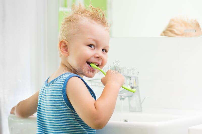 Barn som borstar tänder i badrum royaltyfria foton