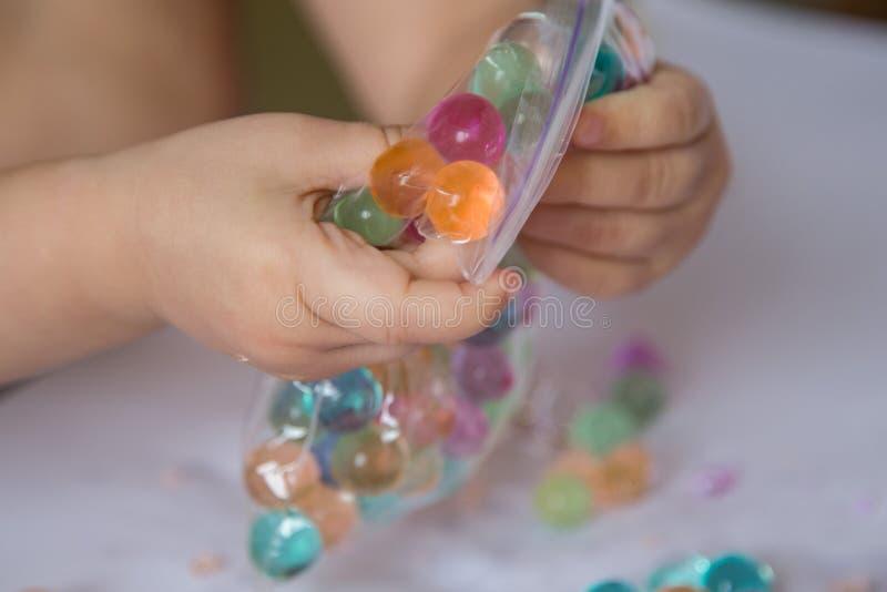 Barn som bryter hydrogelpärlorna i en plast- vinandepacke royaltyfria foton