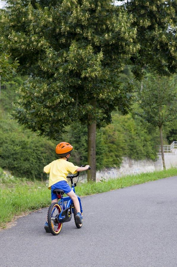 Barn som cyklar på en bana royaltyfri foto