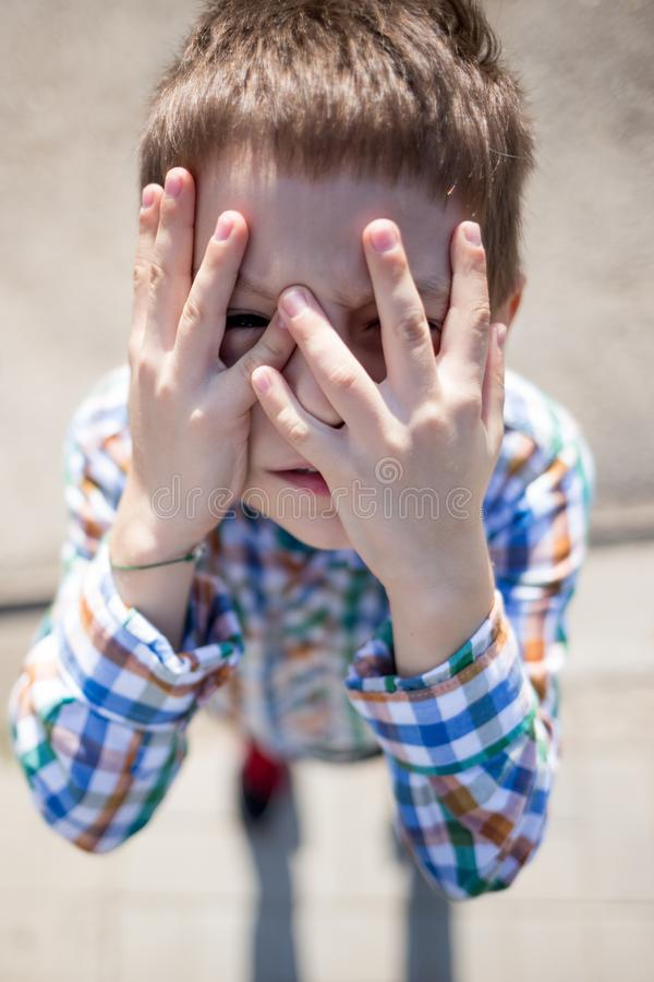 Barn som döljer hans framsida med skräck royaltyfria bilder