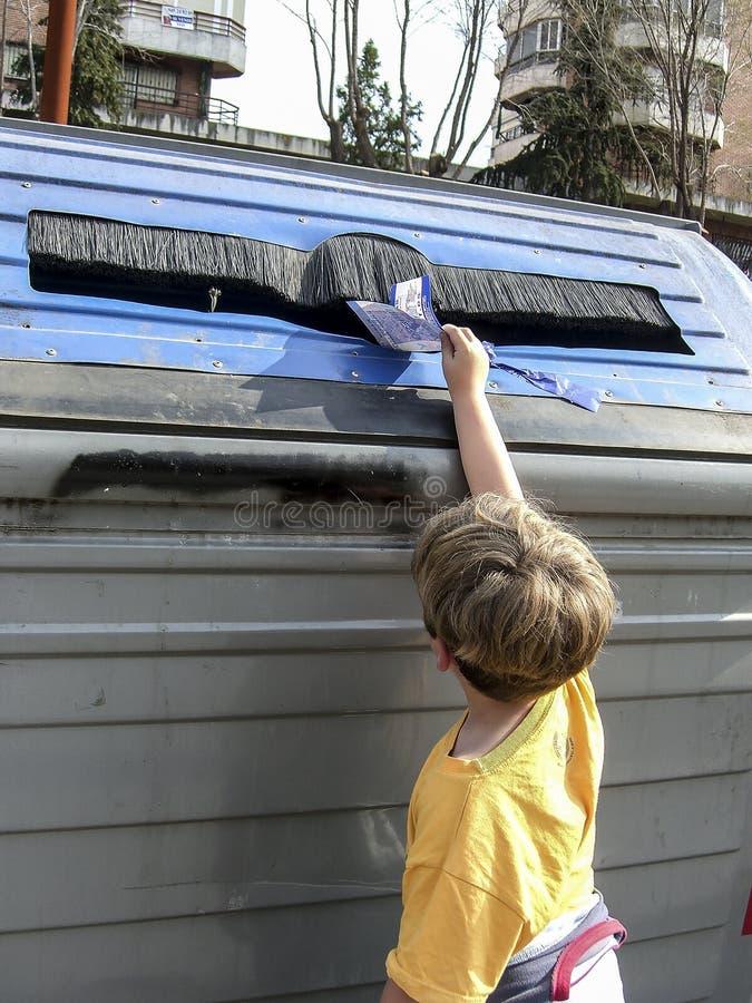 Barn som drar en papp in i återvinningbehållaren för papper arkivfoton