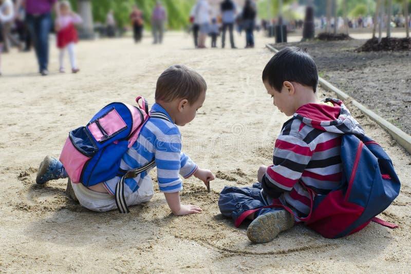 Barn som drar in i sand med pinnen royaltyfri fotografi