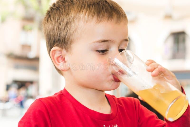 Barn som dricker en sodavatten i ett exponeringsglas arkivfoton