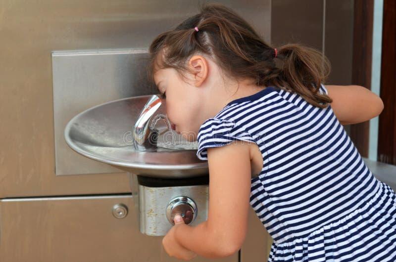 Barn som dricker från den utomhus- vattenspringbrunnen arkivfoto