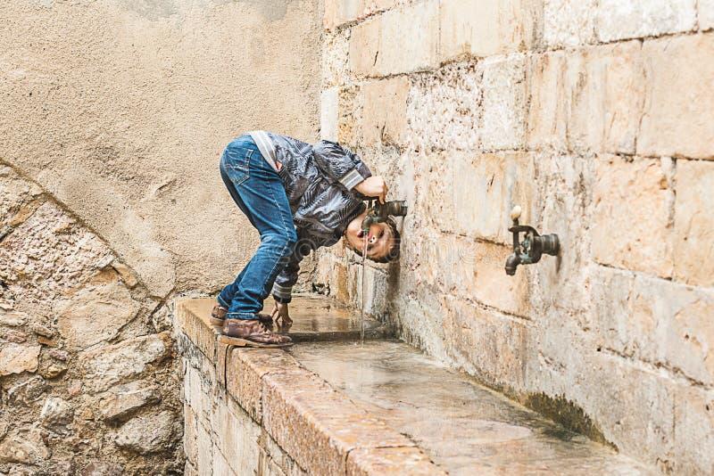 Barn som dricker från en vattenkälla royaltyfri foto