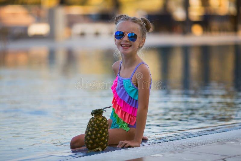 Barn som dricker fruktsaft i simbassängstång fotografering för bildbyråer