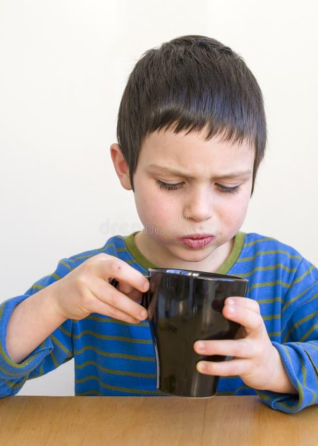 Barn som dricker kopp te arkivbild
