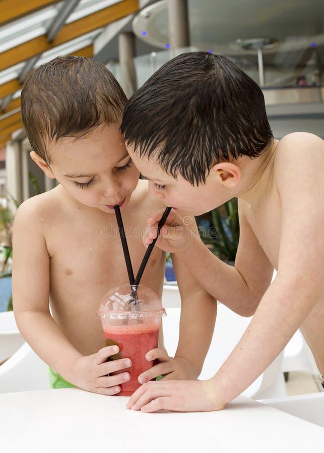 Barn som dricker och delar fruktsaft eller coctailen arkivfoto