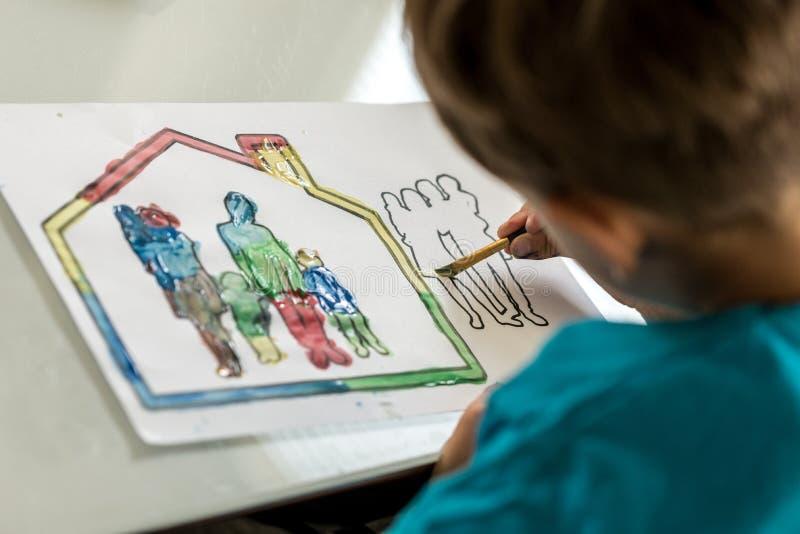 Barn som färgar i en skissa av en familj som använder en målarpensel arkivbild