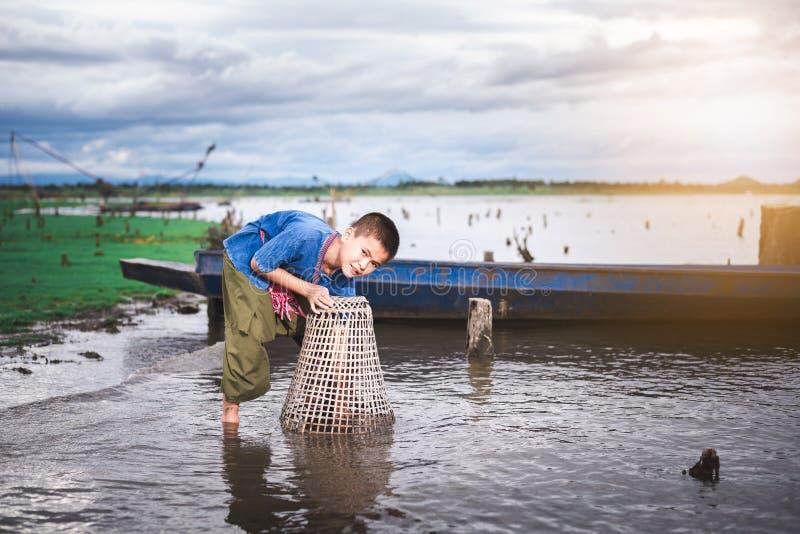Barn som fångar fisken och att ha gyckel i kanalen Livstil av barn fotografering för bildbyråer