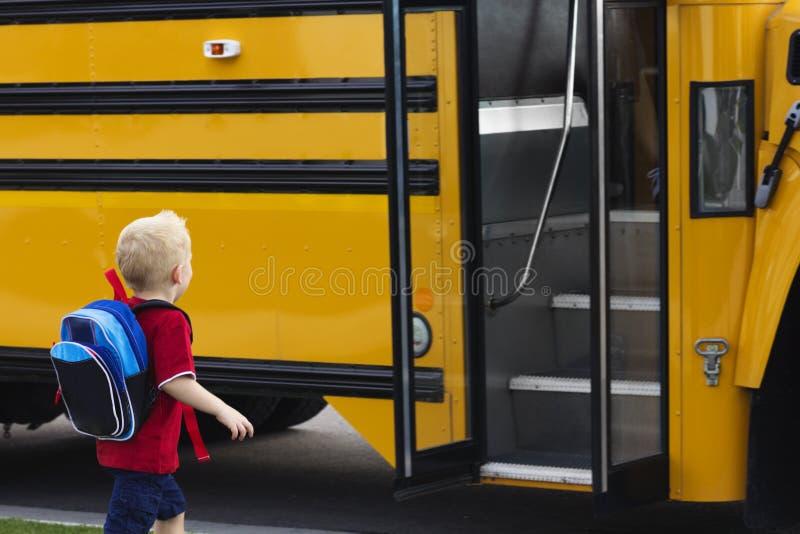 Barn som får på en skolbuss royaltyfri foto