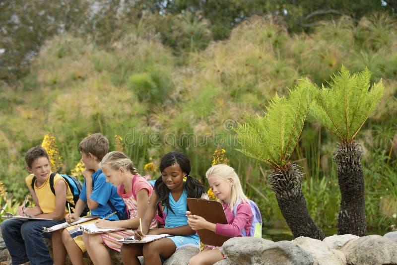 Barn som förbereder anmärkningar under fälttur arkivfoto