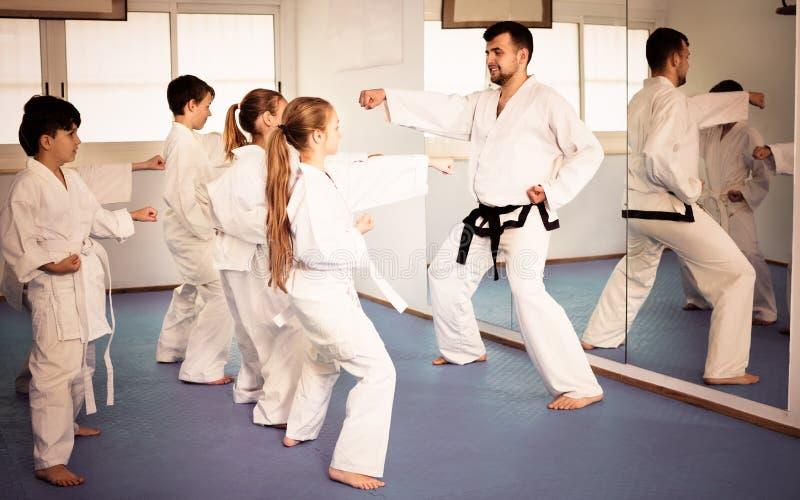Barn som försöker krigs- flyttningar i karategrupp arkivbilder