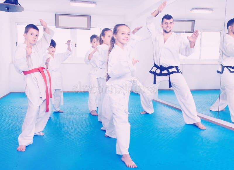 Barn som försöker krigs- flyttningar i karategrupp royaltyfri fotografi