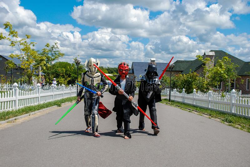 Barn som förställas i Star Wars dräkter: Pilstor trähammare, Darth Vader med svärd Darth Vader royaltyfri fotografi