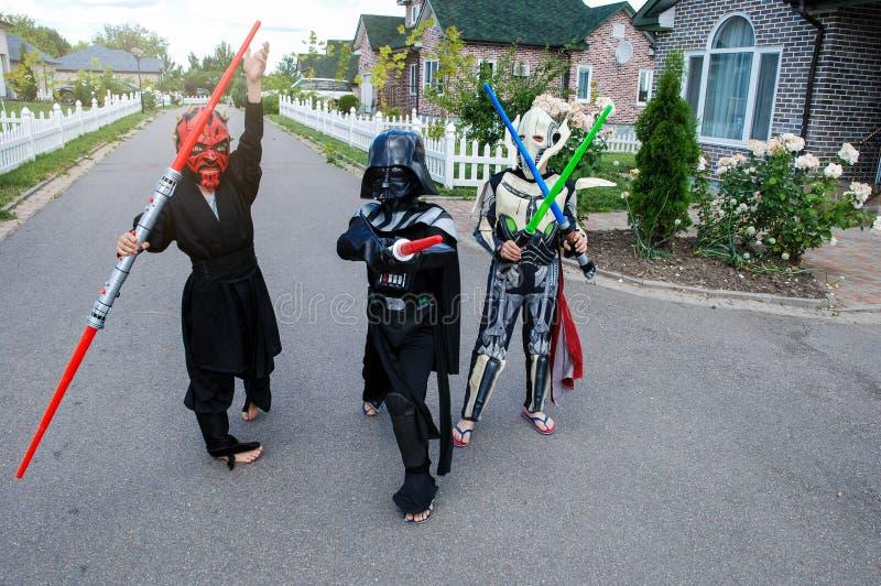 Barn som förställas i Star Wars dräkter: Pilstor trähammare, Darth Vader med svärd Darth Vader royaltyfria bilder