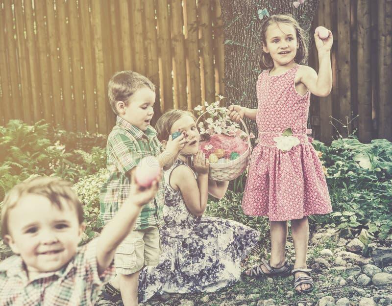 Barn som finner ägg på en Retro jakt för påskägg - royaltyfria bilder