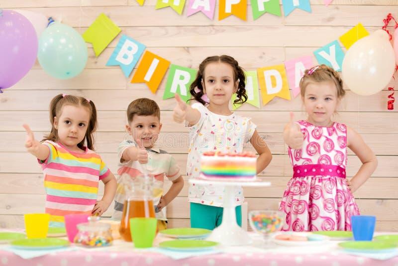 Barn som firar f?delsedagpartiet Lyckliga ungar visar upp tummar royaltyfria bilder