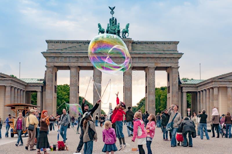 Barn som framme spelar med slagsåpbubblor av den Brandenburg porten, Berlin arkivfoton