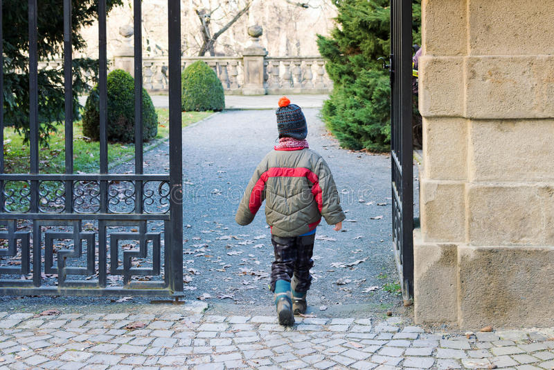 Barn som går till och med en port in i en parkera eller en trädgård royaltyfri bild
