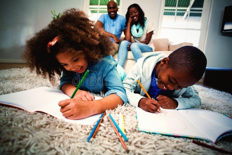 Barn som gör deras läxa med föräldrar i bakgrund royaltyfri bild
