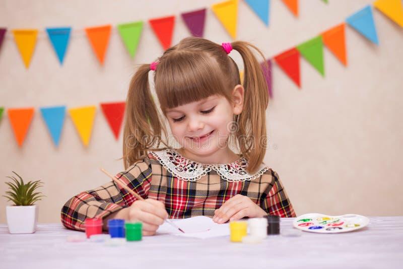 Barn som gör det hemlagade hälsningkortet Lilla flickan målar hjärta på hemlagat hälsa kort som gåvan för mors dag royaltyfria foton