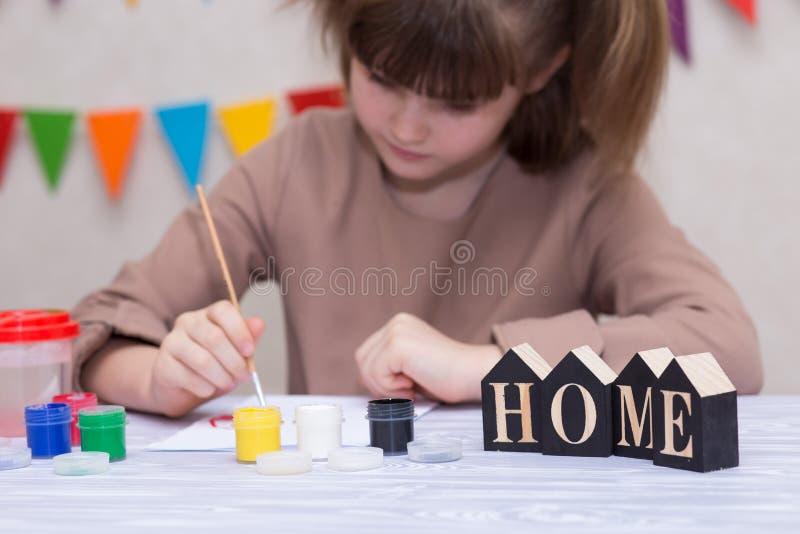 Barn som gör det hemlagade hälsningkortet Lilla flickan målar hjärta på hemlagat hälsa kort som gåvan för mors dag fotografering för bildbyråer