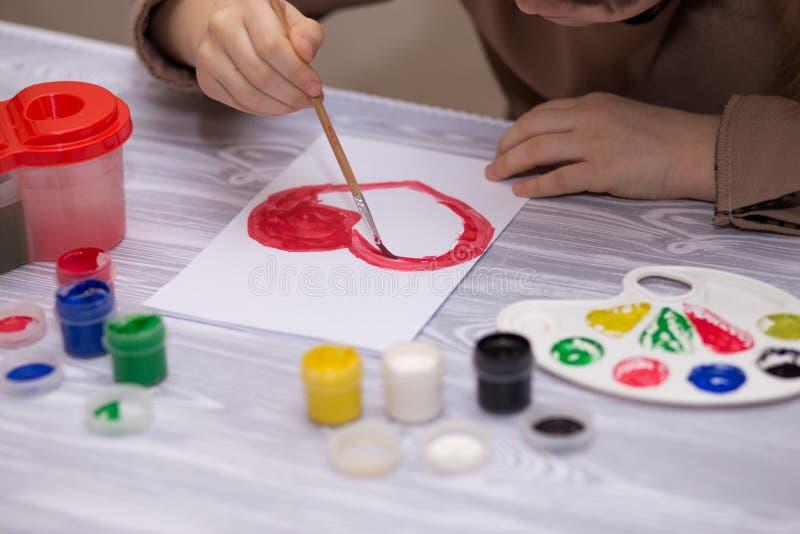 Barn som gör det hemlagade hälsningkortet Lilla flickan målar hjärta på hemlagat hälsa kort som gåvan för mors dag arkivfoton