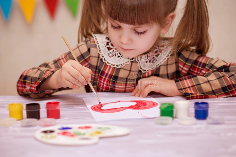Barn som gör det hemlagade hälsningkortet Lilla flickan målar hjärta på hemlagat hälsa kort som gåvan för mors dag royaltyfri bild