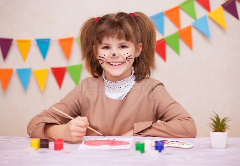 Barn som gör det hemlagade hälsningkortet Lilla flickan målar hjärta på hemlagat hälsa kort som gåvan för mors dag royaltyfri fotografi