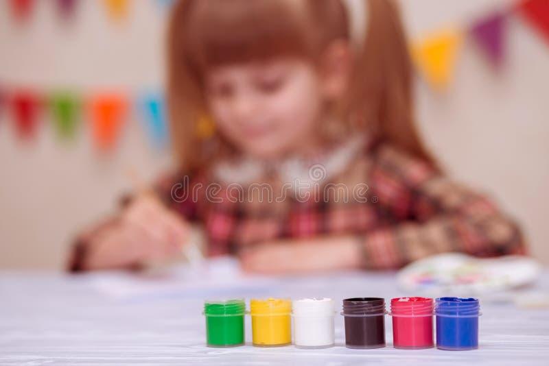 Barn som gör det hemlagade hälsningkortet Lilla flickan målar hjärta på hemlagat hälsa kort som gåvan för mors dag royaltyfria bilder
