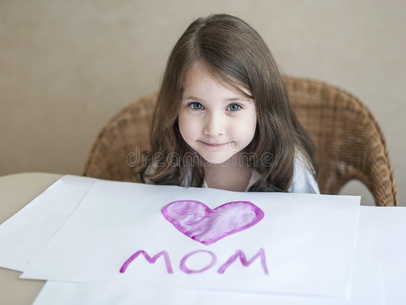 Barn som gör det hemlagade hälsningkortet Lite målar flickan en hjärta på ett hemlagat hälsningkort som en gåva för mors dag royaltyfria foton