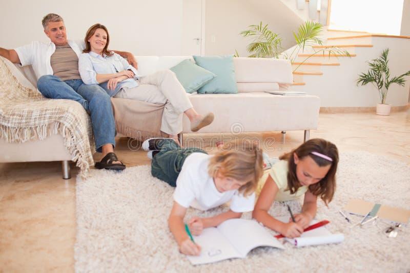Barn som gör läxa med föräldrar bak dem royaltyfri foto