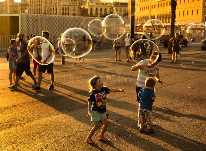 Barn som gör stora såpbubblor royaltyfri fotografi