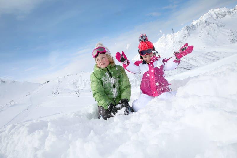Barn som har gyckel i snön royaltyfria foton