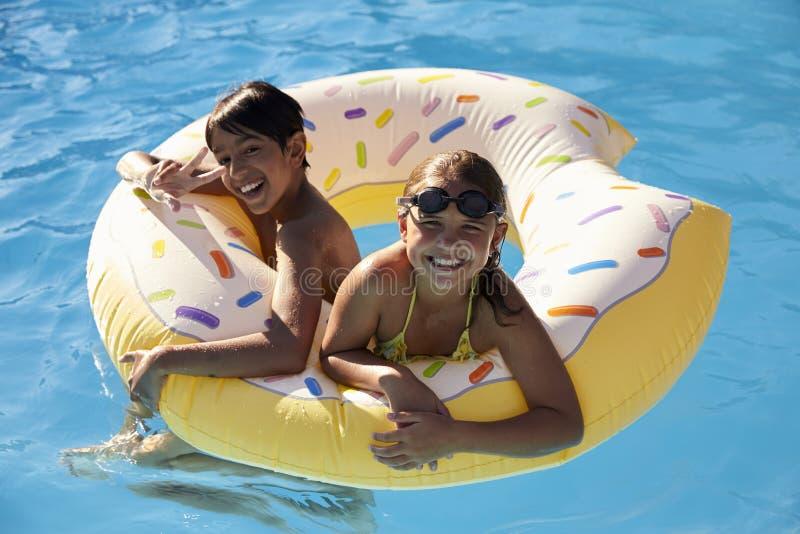 Barn som har gyckel med uppblåsbar i utomhus- simbassäng arkivbild