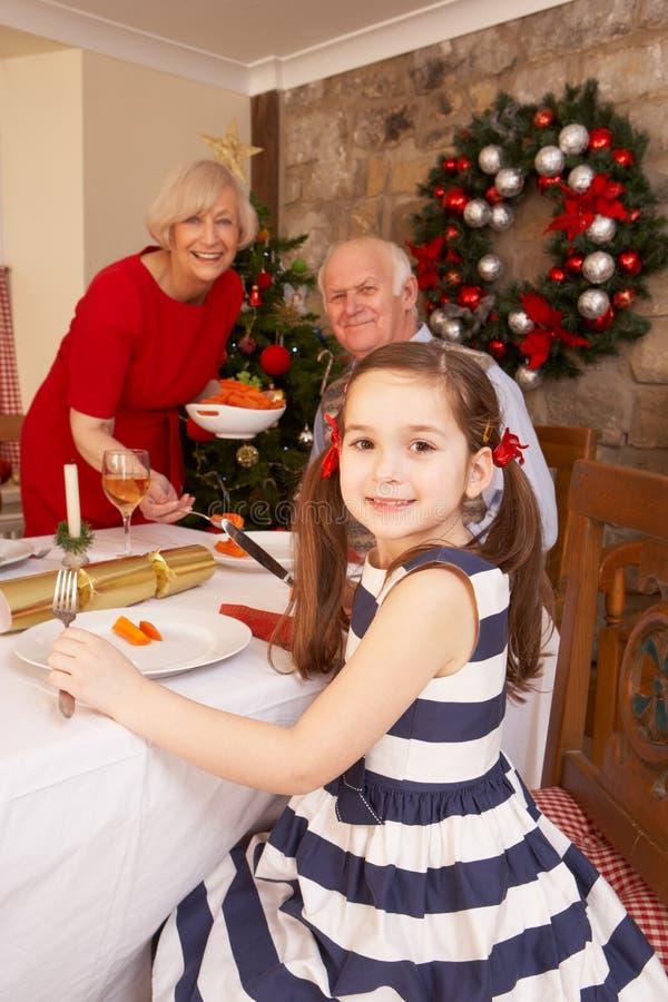 Barn som har julmatställe med morföräldrar royaltyfri fotografi