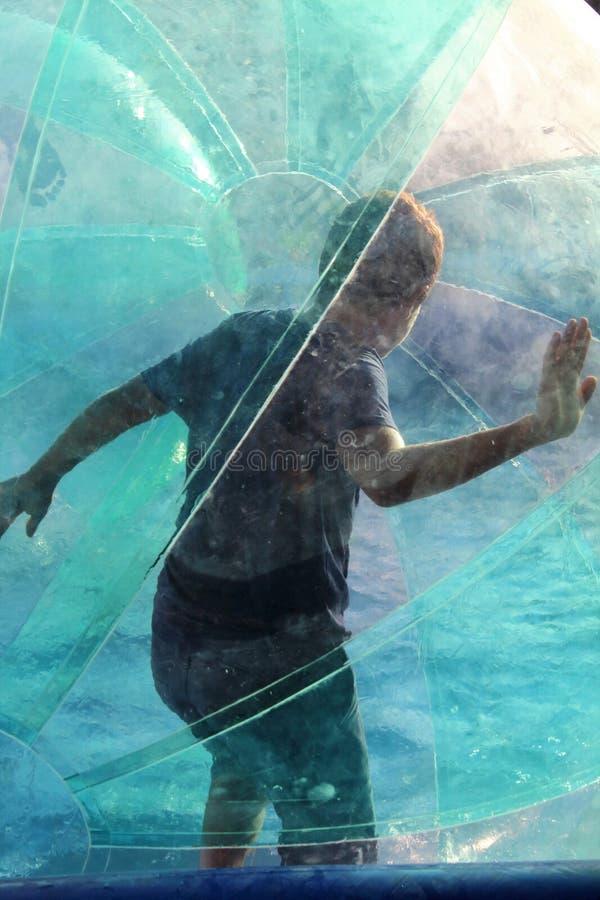 Barn som har kul i den uppblåsbara boll som flyter på vattnet i poolen arkivbilder