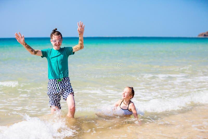 Barn som har kul på stranden fotografering för bildbyråer