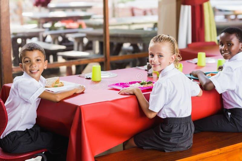 Barn som har lunch under avbrottstid i skolakafeteria arkivbilder