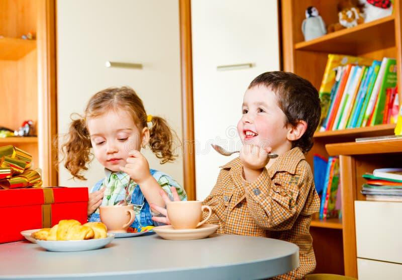 barn som har tea royaltyfri bild